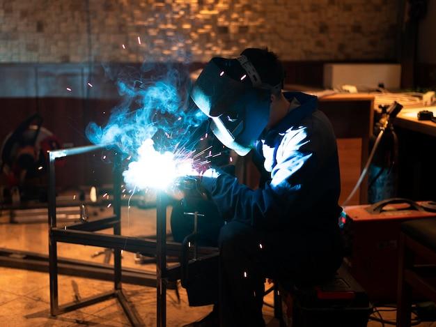 Mężczyzna z maską spawającą metal w atelier