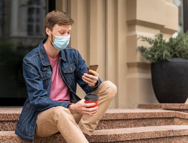 Mężczyzna z maską sprawdza swój telefon