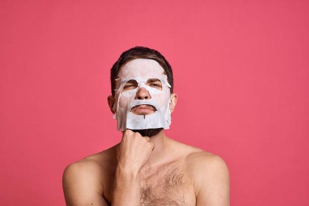 Mężczyzna z maską z tkaniny kosmetycznej na twarzy