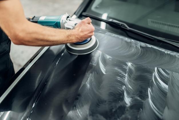 Mężczyzna z maszyną do polerowania czyści maskę samochodu