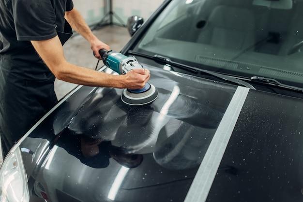 Mężczyzna z maszyną do polerowania czyści samochód