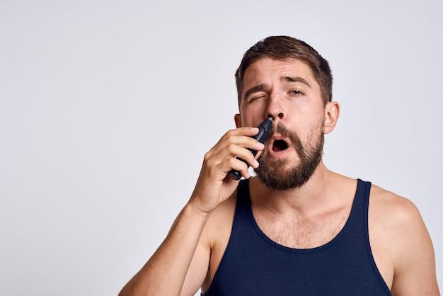 Mężczyzna z maszyną do usuwania włosów z nosa w czarnym t-shircie na jasnym tle