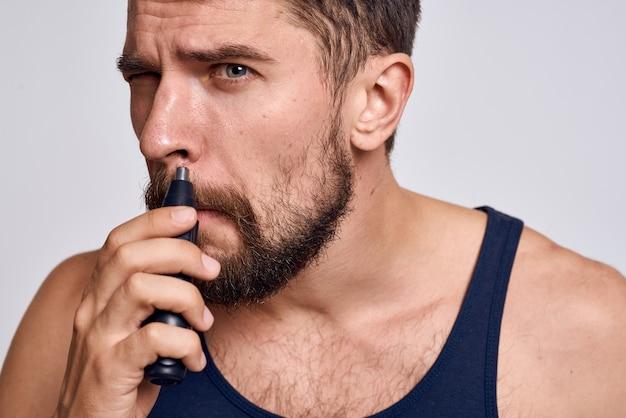 Mężczyzna z maszyną do usuwania włosów z nosa