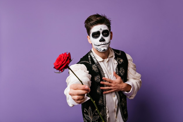 Mężczyzna z meksykańskim martwym makijażem, trzymając czerwony kwiat. emocjonalny facet w tradycyjnych hiszpańskich strojach.