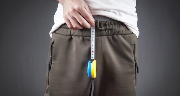 Mężczyzna z miarką mierzy rozmiar swojego penisa.