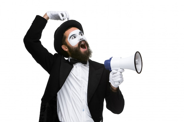 Mężczyzna z mimem twarzy krzyczy do megafonu