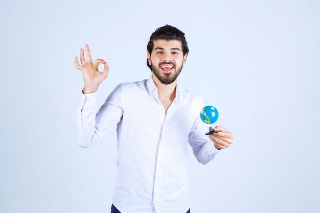 Mężczyzna z mini globusem, który się tym cieszy