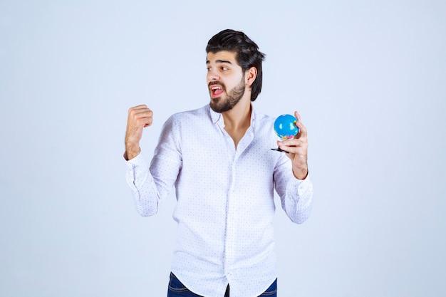Mężczyzna z mini-globusem pokazującym pięść