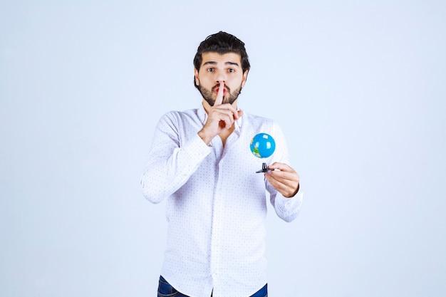 Mężczyzna z mini-globusem proszącym o ciszę