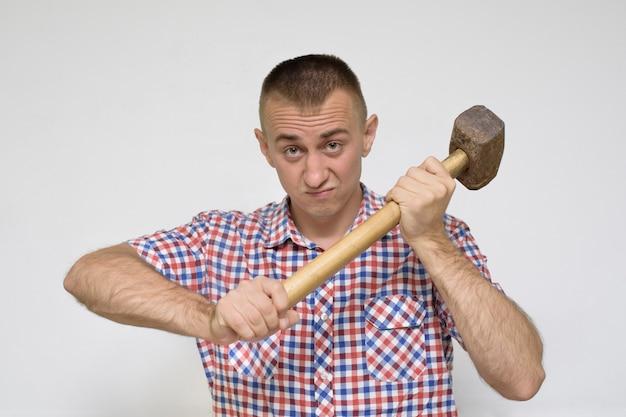 Mężczyzna z młotem na białej ścianie. koncepcja pracy