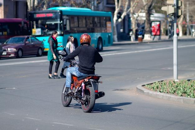 Mężczyzna z motocyklem jadący przez skrzyżowanie