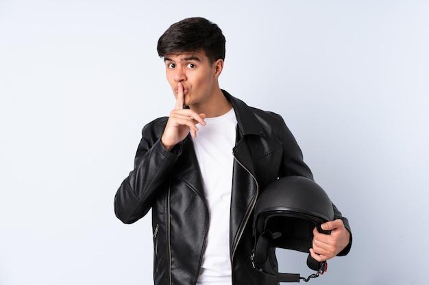Mężczyzna z motocyklowym hełmem nad odosobnionym błękitem robi cisza gestowi