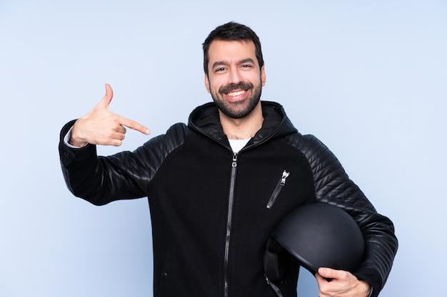 Mężczyzna z motocyklu hełmem nad odosobnioną ścianą