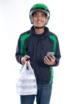 Mężczyzna z mundurową kurtką i hełmem dostarcza jedzenie