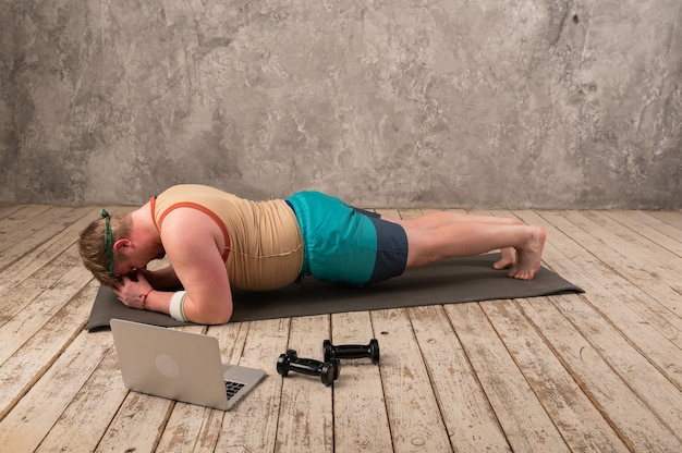 Mężczyzna z nadwagą ćwiczy, robi ćwiczenia rozciągające na macie do jogi, ogląda filmy fitness online na laptopie w domu.
