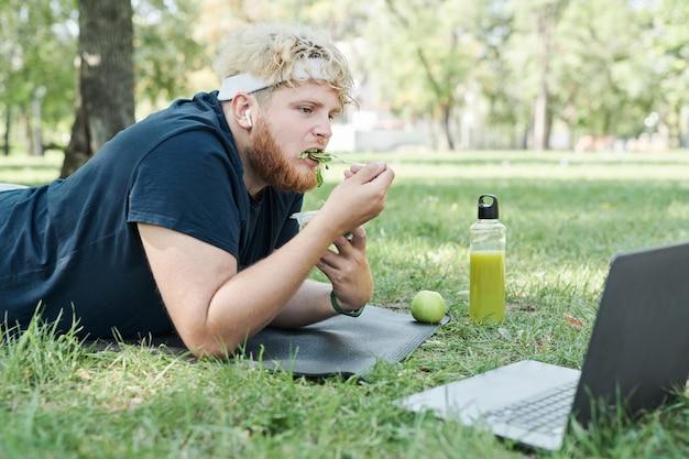 Mężczyzna z nadwagą leżący na trawie jedzący zdrową żywność i oglądając coś na laptopie po sporcie...