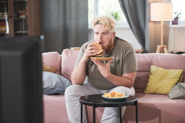 Mężczyzna z nadwagą siedzi na kanapie je burgera z frytkami i ogląda film w telewizji w pokoju ...