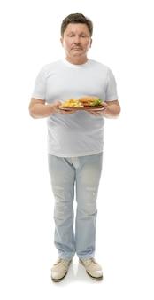 Mężczyzna z nadwagą trzyma talerz z fast foodami na białej powierzchni