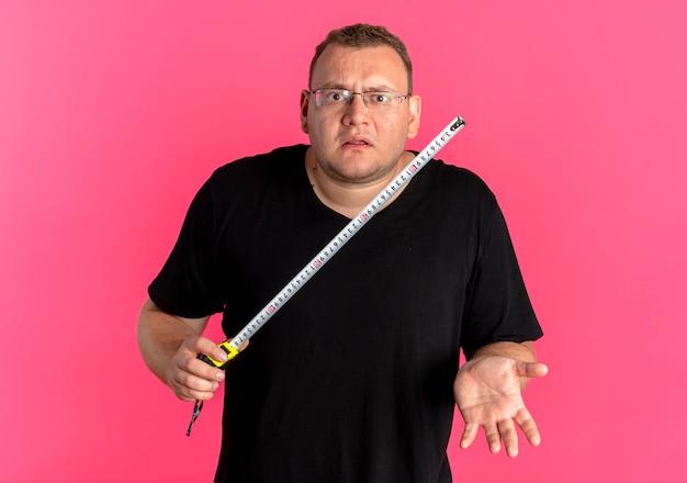 Mężczyzna z nadwagą w okularach na sobie czarną koszulkę trzymający linijkę wygląda na zdezorientowanego, stojącego na różowej ścianie bez odpowiedzi