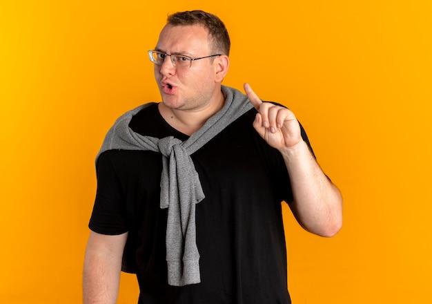 Mężczyzna z nadwagą w okularach na sobie czarną koszulkę z zmarszczoną miną pokazuje palec wskazujący na pomarańczowo