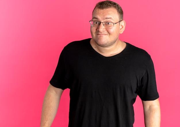 Mężczyzna z nadwagą w okularach na sobie czarną koszulkę zdezorientowany, uśmiechając się na różowo