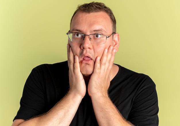 Mężczyzna z nadwagą w okularach ubrany w czarną koszulkę, patrząc na bok zaskoczony i zdumiony, stojąc nad jasną ścianą z rękami na twarzy