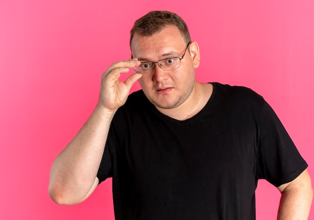 Mężczyzna z nadwagą w okularach, ubrany w czarną koszulkę, patrząc na coś zdezorientowanego na różowo