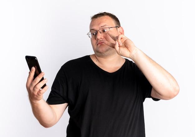 Mężczyzna z nadwagą w okularach, ubrany w czarną koszulkę, patrząc na ekran swojego smartfona w trybie online, pokazujący znak zwycięstwa stojący nad białą ścianą