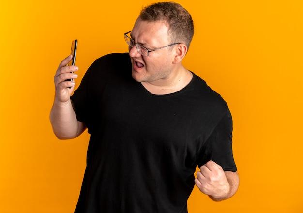 Mężczyzna z nadwagą w okularach, ubrany w czarną koszulkę, patrząc na ekran swojego smartfona, zaciskając pięść bardzo zdenerwowany z powodu pomarańczy