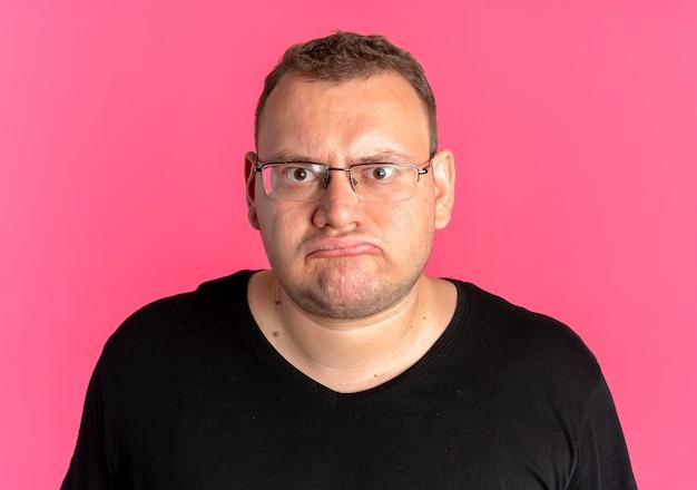 Mężczyzna z nadwagą w okularach ubrany w czarną koszulkę patrzy na aparat niezadowolony z różu