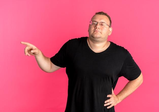 Mężczyzna z nadwagą w okularach, ubrany w czarną koszulkę, pewny siebie, wskazujący palcem wskazującym w bok, stojący nad różową ścianą