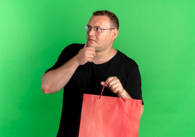 Mężczyzna z nadwagą w okularach, ubrany w czarną koszulkę, trzymający papierowe torby, patrząc zdziwiony, stojąc nad zieloną ścianą