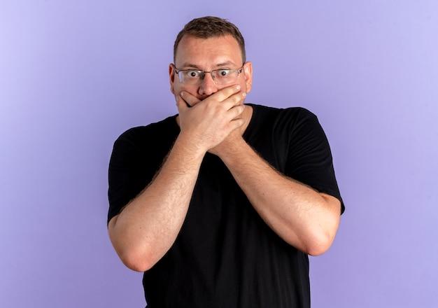 Mężczyzna z nadwagą w okularach ubrany w czarną koszulkę zakrywającą usta z rękami wstrząśniętymi na niebiesko