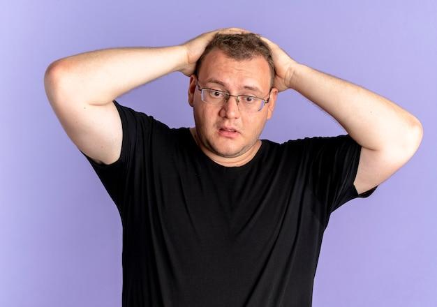 Mężczyzna z nadwagą w okularach, ubrany w czarną koszulkę, zdezorientowany, dotykając głowy za pomyłkę stojąc nad niebieską ścianą