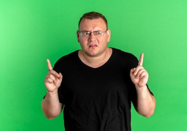 Mężczyzna z nadwagą w okularach, ubrany w czarny t-wygląd, zdezorientowany, wskazujący palcami w górę nad zieloną ścianą