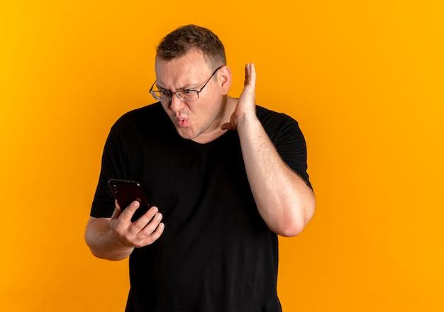 Mężczyzna z nadwagą w okularach w czarnej koszulce trzymający smartfona zaciskająca pięść krzyczący ze zdezorientowanym wyrazem twarzy stojący nad pomarańczową ścianą