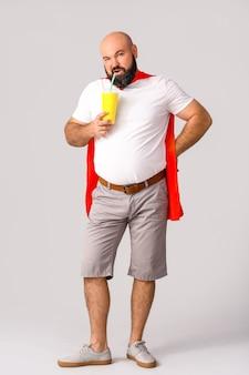 Mężczyzna z nadwagą w pelerynie iz colą na szarym tle. koncepcja odchudzania