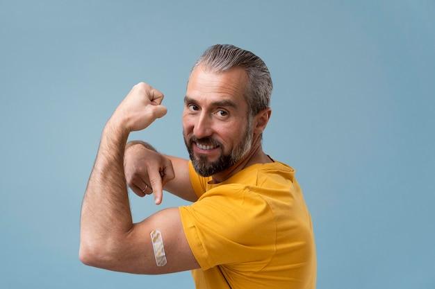 Mężczyzna z naklejką na ramieniu po otrzymaniu szczepionki