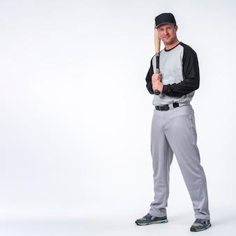 Mężczyzna z nakrętką pozuje z baseballem