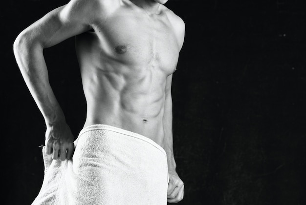 Mężczyzna z napompowanym ciałem okrywa się ręcznikiem studio fitness. zdjęcie wysokiej jakości