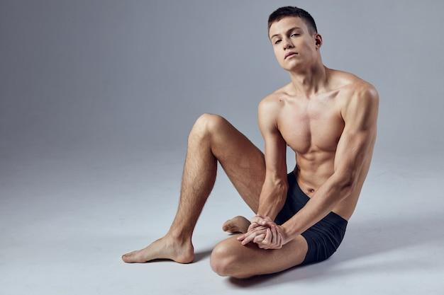Mężczyzna z napompowanym ciałem pozuje siedzący na podłodze
