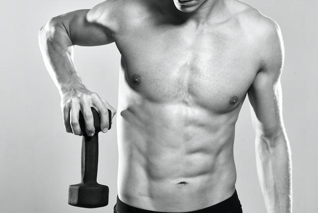 Mężczyzna z napompowanym torsem podczas ćwiczeń mięśni pozuje