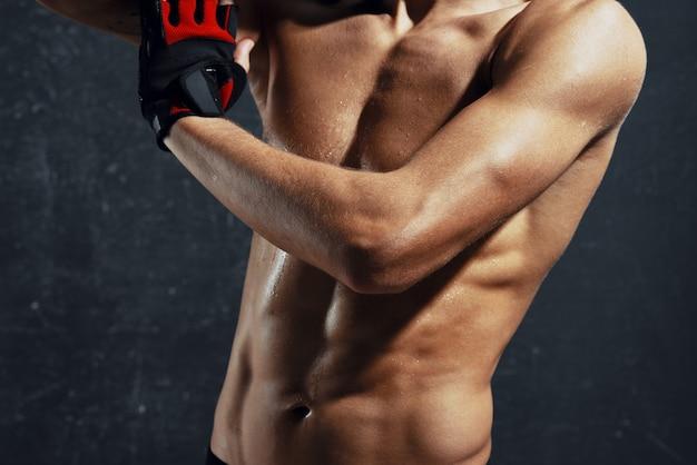 Mężczyzna z napompowanymi ręcznikami tułowia w dłoniach i modelem motywacji do treningu