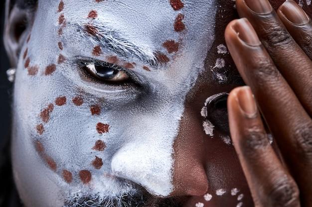 Mężczyzna z narodowym etnicznym makijażem na twarzy