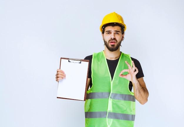 Mężczyzna z narzędziami, trzymający folder projektu i pokazujący znak satysfakcji.