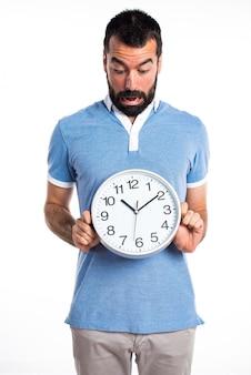 Mężczyzna z niebieską koszulę gospodarstwa zegara