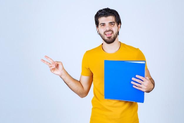 Mężczyzna z niebieską teczką dający przyjazne i spokojne pozy.
