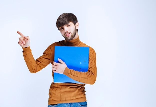 Mężczyzna z niebieską teczką pokazującą lewą stronę.