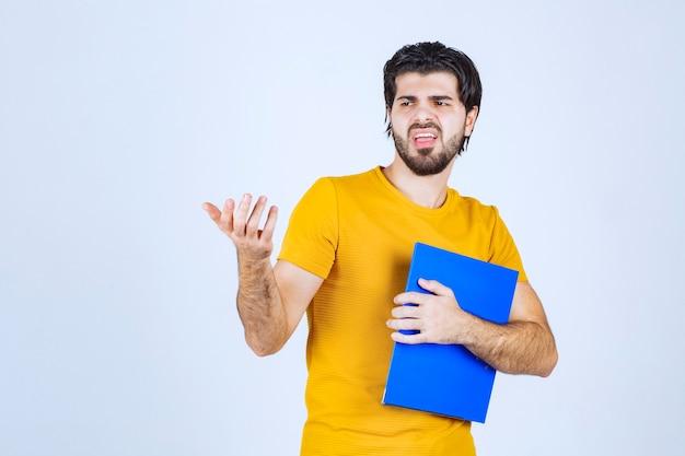 Mężczyzna z niebieską teczką, wskazując kolegę na lewą stronę i rozmawiający z emocjami.
