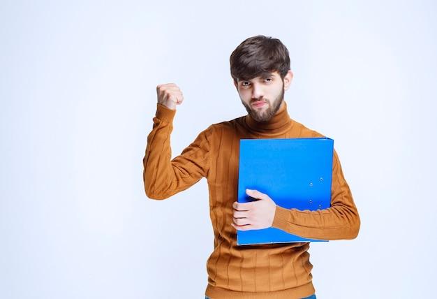 Mężczyzna z niebieską teczką wygląda na potężnego i usatysfakcjonowanego.